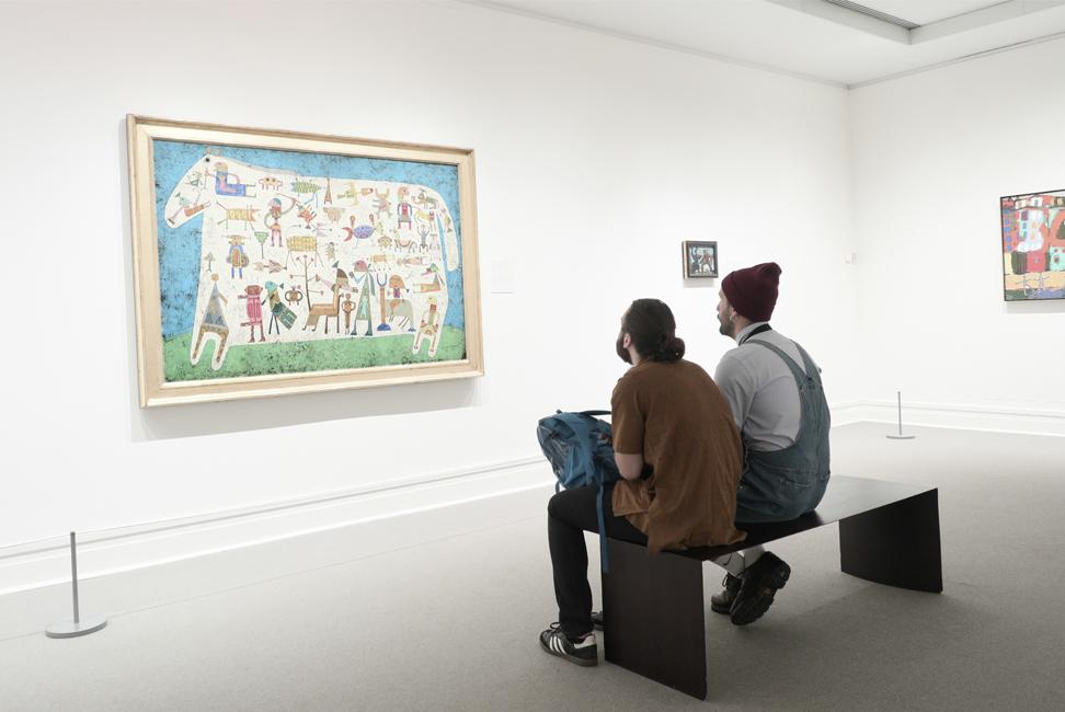 Hombres jóvenes analizando un cuadro en una galería de arte