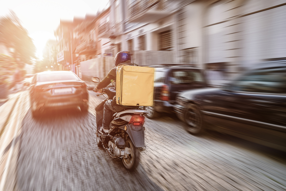 Motoboy andando a toda velocidad en calle de adoquines