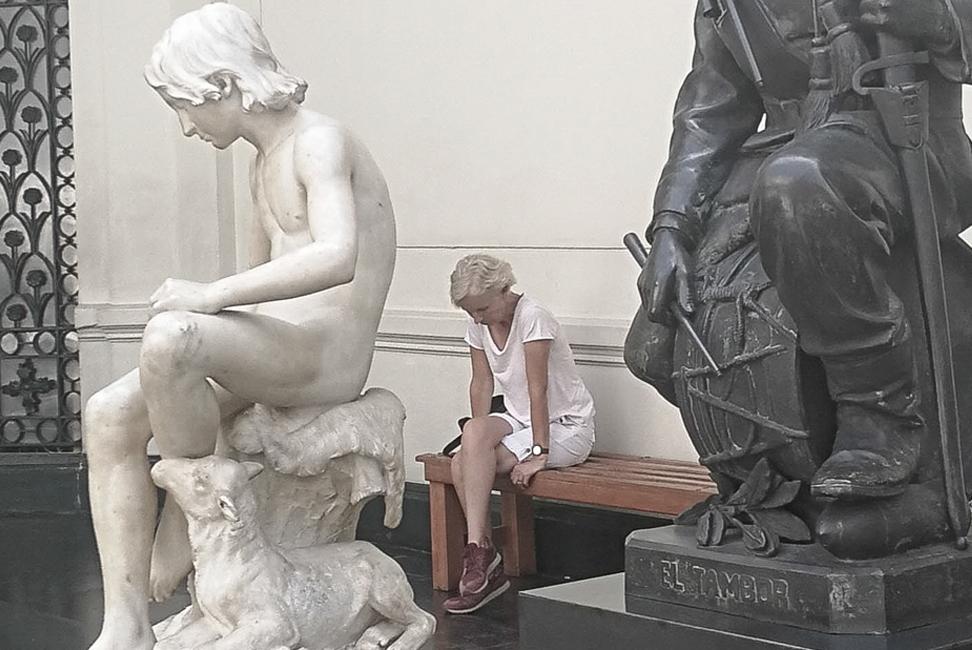 Mujer sentada en un banco de madera en una galería de arte. En primer plano dos esculturas.