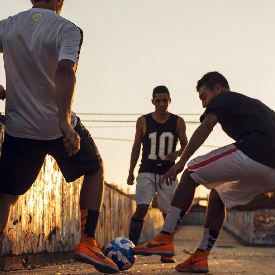 Foto de tres jóvenes jugando fútbol