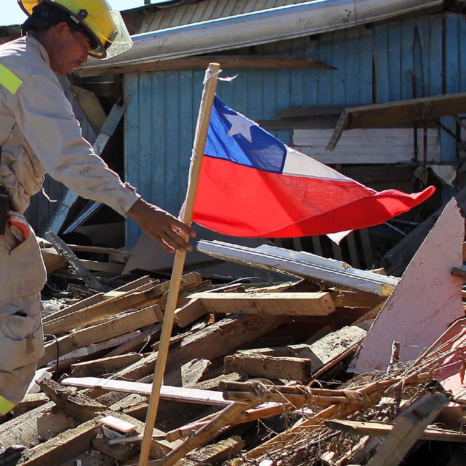 Foto de un bombero con una bandera chilena entre escombros